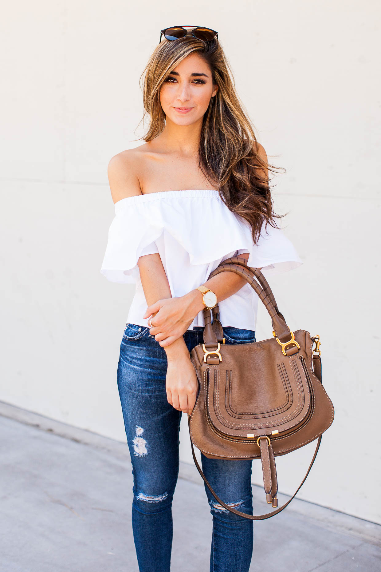 """The Darling Detail wearing a white Topshop Poplin Bardot Top with AG """"The Legging"""" Ankle Jeans and Steve Madden """"Kierra"""" Platform Sandals—and holding the Chloe Marcie Leather Satchel."""